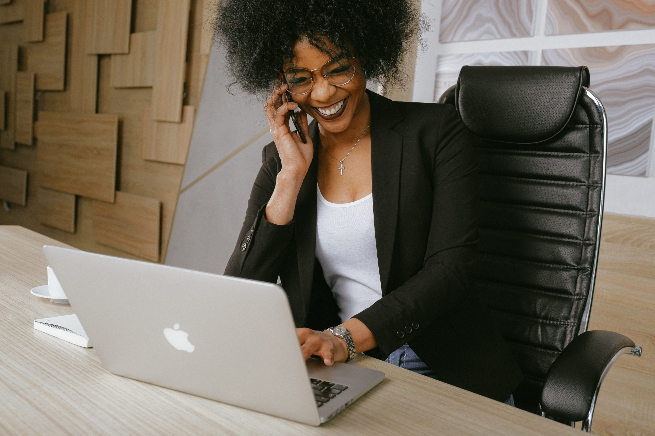 Woman in black blazer smiling and speaking on her mobile phone at her work desk.